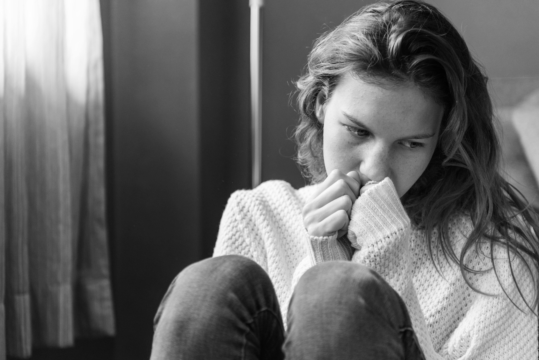 Kvinne sitter alene i et rom