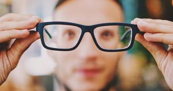 Mann setter på briller. Foto.