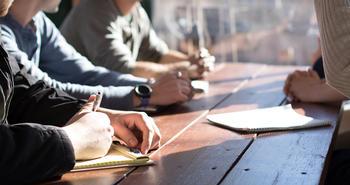Personer sitter rundt et bord. Foto.