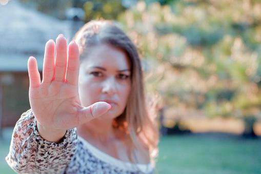 Kvinne holder hånden for opp for stanse en handling