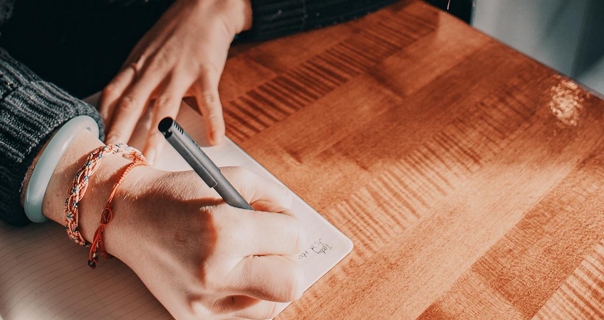 Person skriver på notatblokk. Foto.