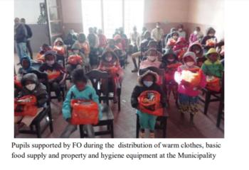 Bilde av mange barn som sitter på stoler i et klasserom. Alle har hver sin oransje plastpose i fanget. De fleste barna har munnbind på.