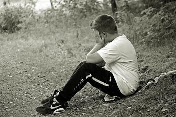 Lys gutt med hvit t-skjorte og svart joggebukse sitter på bakken. Han støtter albuene mot knærne og holder hendene foran ansiktet