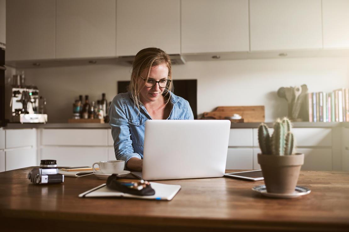 Illustrasjonsfoto: person foran data på kjøkken