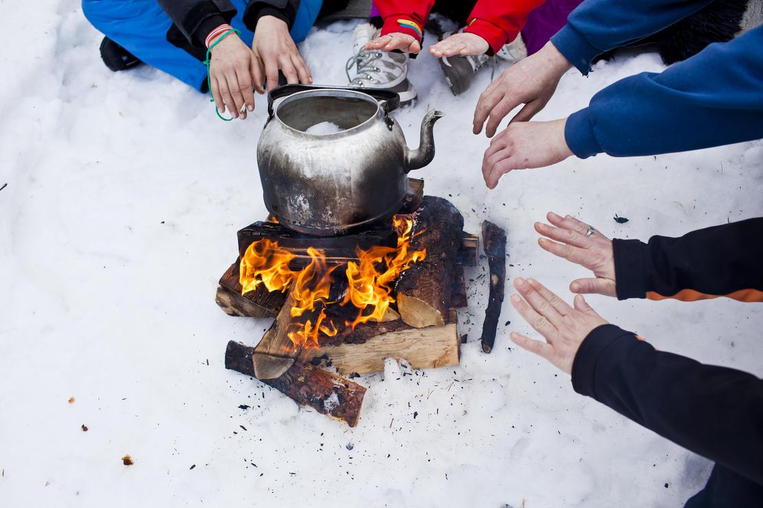 Illustrasjonsfoto: hender som varmer seg over bål i snøen
