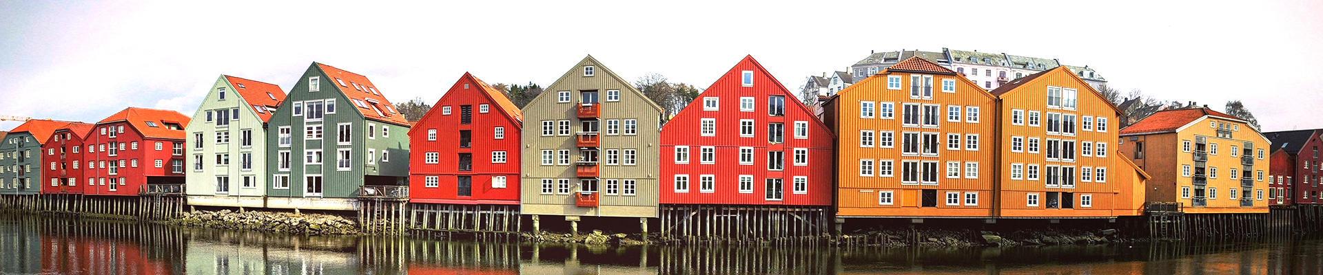 Panoramabilde av en bryggerekke med store bygninger med sterke farger i grønt, rødt, hvitt, grått og gult. Bryggene står langs en elv.